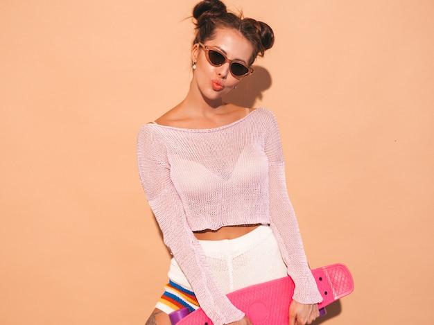 Mulher bonita jovem sorridente sexy hipster em óculos de sol. garota na moda no tópico casaco de malha de verão, shorts. fêmea positiva enlouquecendo com skate centavo rosa, isolado na parede bege. Foto gratuita