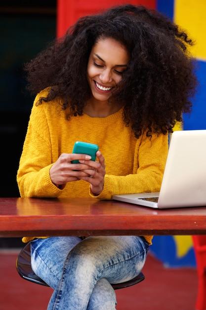 Mulher bonita, ler a mensagem de texto no celular no café Foto Premium