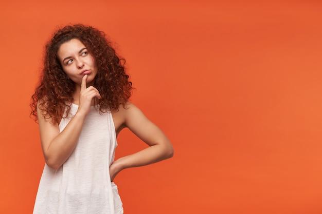 Mulher bonita, linda garota com cabelo ruivo cacheado. usando uma blusa branca sem ombros. tocando seu lábio e pensando. observando à direita no espaço da cópia, isolado sobre a parede laranja Foto gratuita