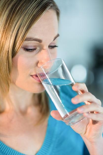 Mulher bonita loira bebendo um copo de água Foto Premium