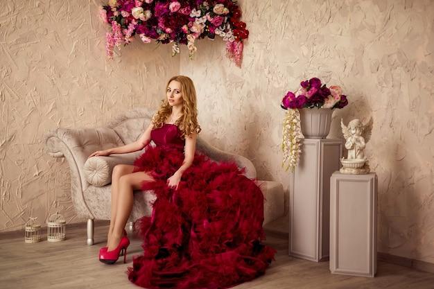 Mulher bonita loira elegante no sofá vestido de borgonha Foto Premium