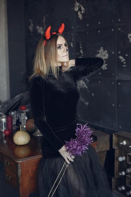 Mulher bonita maquiagem de halloween com penteado loiro. menina modelo em traje preto. tema de halloween. Foto gratuita