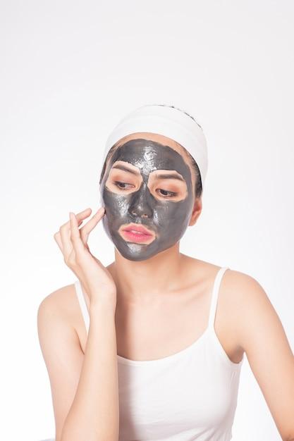 Mulher bonita mascarando o rosto em fundo branco Foto Premium