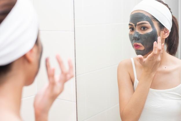 Mulher bonita mascarando o rosto no fundo branco Foto Premium