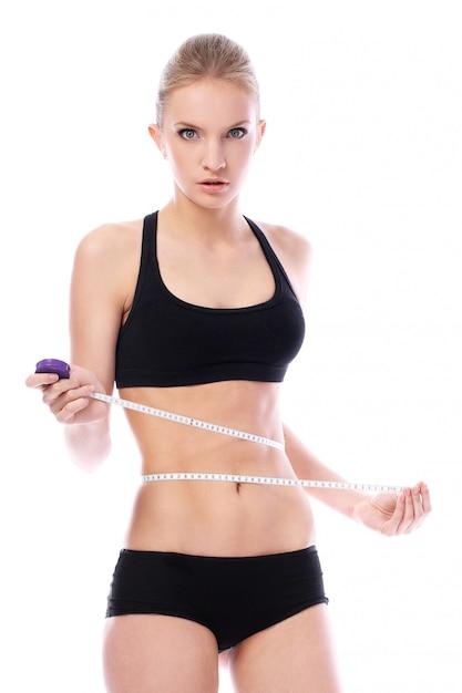 Mulher bonita, medindo sua cintura Foto gratuita