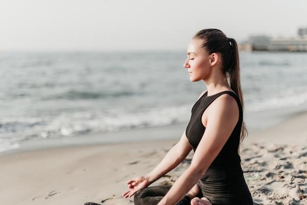 Mulher bonita, meditando e praticando ioga na praia perto do oceano Foto Premium