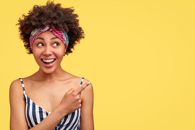 Mulher bonita mestiça com cabelo crespo, sorriso gentil, mostra algo agradável, indica com o dedo indicador na parede amarela em branco. mulher afro-americana encantadora posando em ambientes internos Foto gratuita