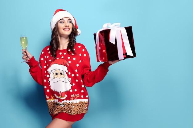 Mulher bonita morena de camisola vermelha com papai noel, taça de champanhe em fundo azul Foto Premium