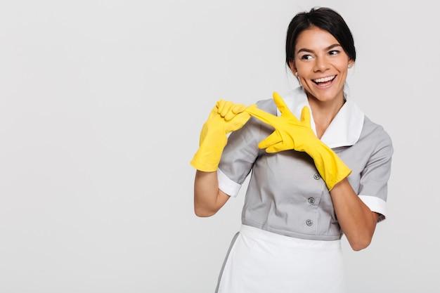 Mulher bonita morena de uniforme cinza, tirando as luvas protetoras amarelas enquanto sorrindo e olhando de lado Foto gratuita