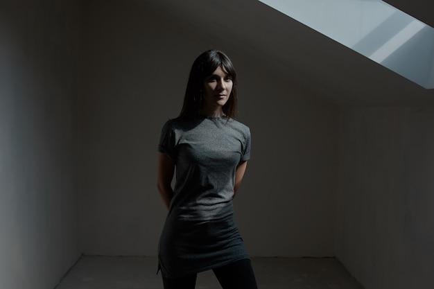 Mulher bonita morena posando no quarto escuro Foto gratuita