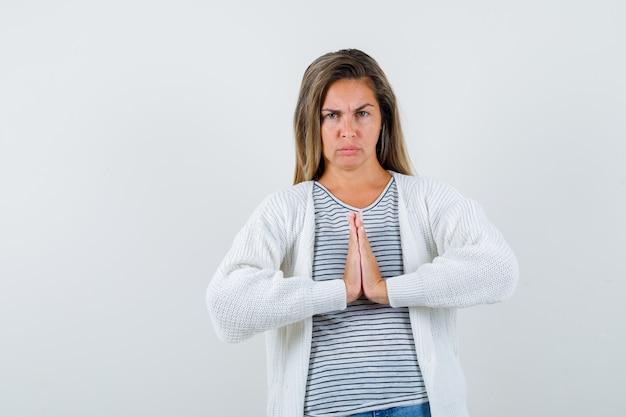 Mulher bonita, mostrando o gesto namastê na jaqueta e olhando sombrio, vista frontal. Foto gratuita