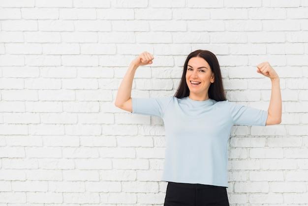 Mulher bonita mostrando os músculos do braço Foto gratuita