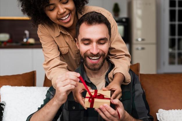 Mulher bonita mulher oferecendo um presente para o namorado Foto gratuita