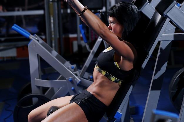 Mulher bonita muscular em uma academia Foto gratuita