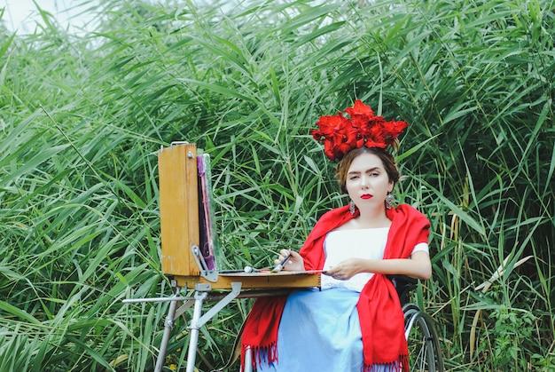 Mulher bonita na cadeira de roda, pintando. Foto Premium