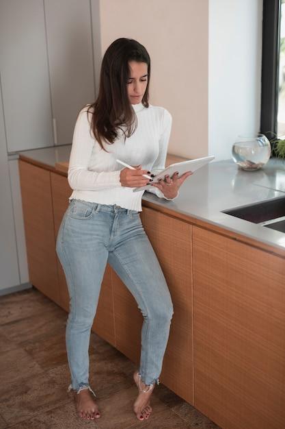 Mulher bonita na cozinha olhando no tablet Foto gratuita