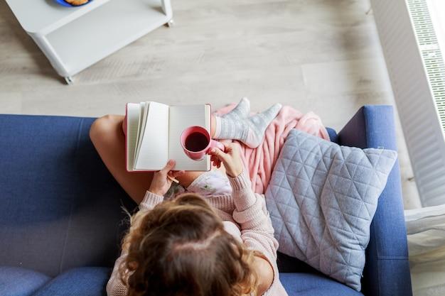 Mulher bonita na leitura do sofá Foto gratuita