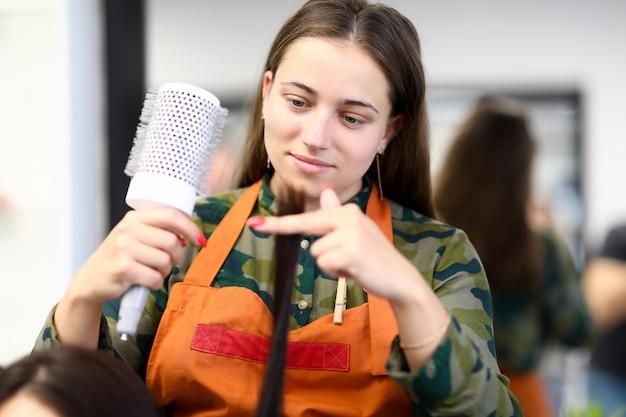 Mulher bonita no avental segurar longa mecha de close-up de cabelo e pente Foto Premium