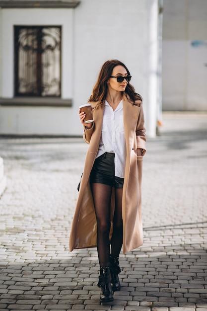 Mulher bonita no casaco bebendo café lá fora na rua Foto gratuita