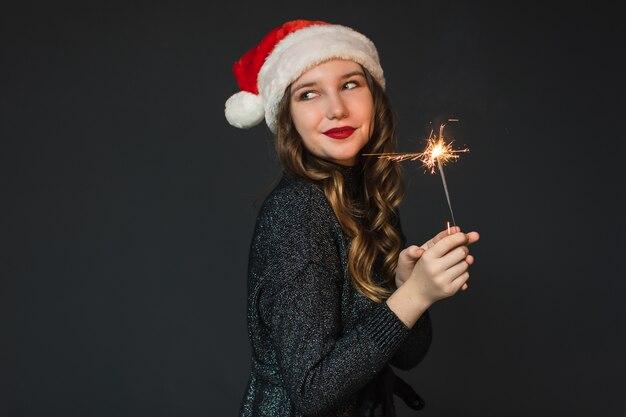 Mulher bonita no chapéu de papai noel detém um diamante Foto Premium