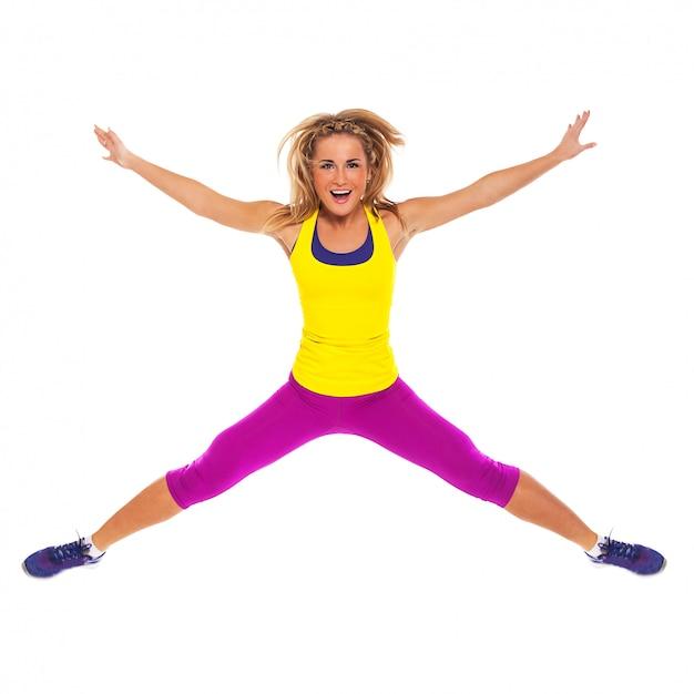 Mulher bonita no desgaste de fitness pulando Foto gratuita