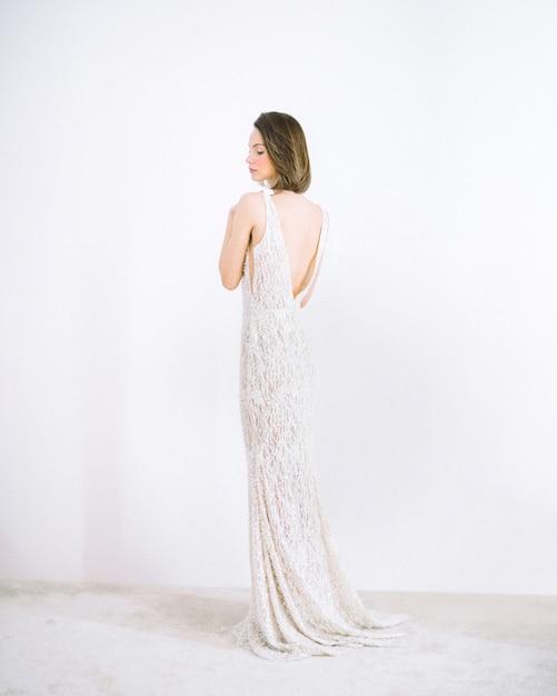 Mulher bonita no vestido longo branco em pé e pensando na sala com branco Foto gratuita