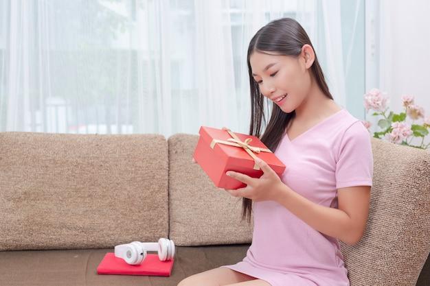 Mulher bonita no vestido rosa, sentado no sofá, abrindo uma caixa de presente. Foto gratuita