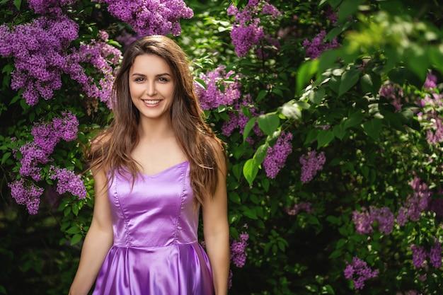 Mulher bonita no vestido roxo posando no parque florescendo. primavera árvores e arbustos Foto Premium