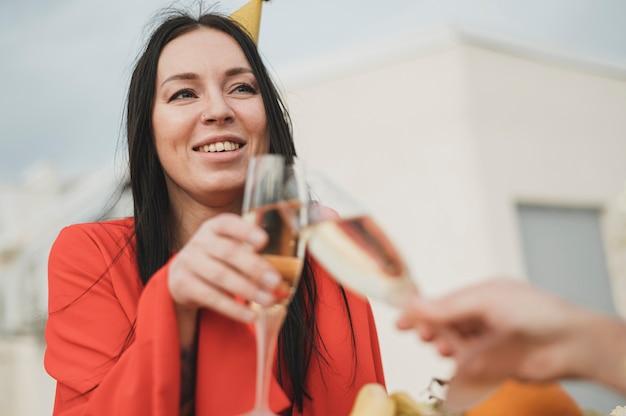 Mulher bonita no vestido vermelho, animar uma taça de champanhe Foto gratuita
