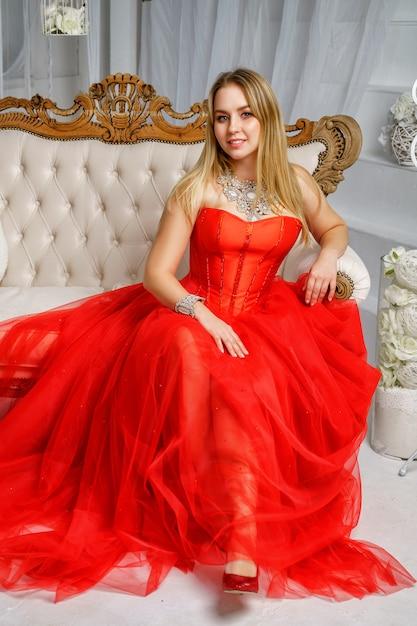 Mulher bonita no vestido vermelho sentado no sofá Foto Premium