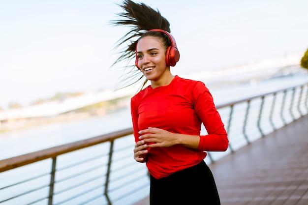 Mulher bonita nova ativa que corre no passeio ao longo do beira-rio Foto Premium