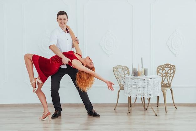 Mulher bonita nova em um vestido vermelho e uma dança do homem isolada em um fundo branco. Foto Premium