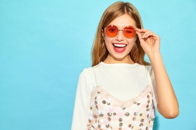 Mulher bonita nova. mulher na moda em roupas de verão casual, piscando em óculos de sol. linguagem corporal de expressão facial de emoção feminina positiva. modelo engraçado isolado na parede azul Foto gratuita