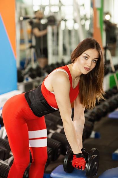 Mulher bonita nova que faz exercícios com peso no gym. a menina de sorriso contente está apreciando com seu processo de treinamento Foto Premium