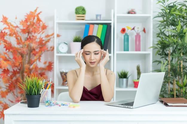 Mulher bonita nova que tem a dor de cabeça que trabalha no computador em casa Foto gratuita