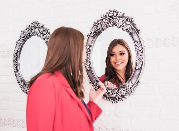 Mulher bonita olhando no espelho Foto gratuita