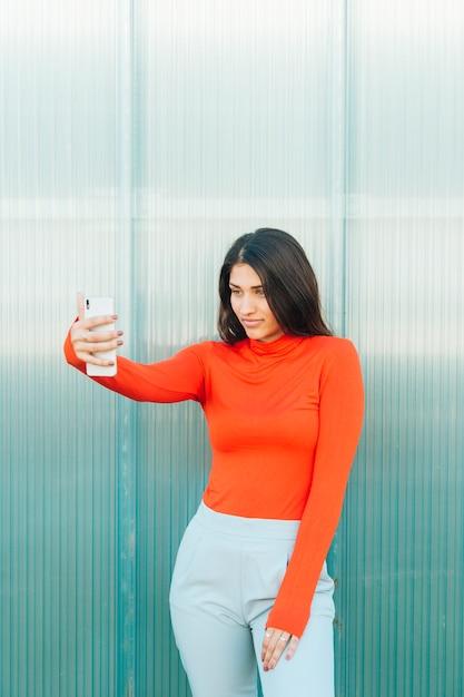 Mulher bonita olhando para a tela do telefone móvel em pé contra a parede Foto gratuita