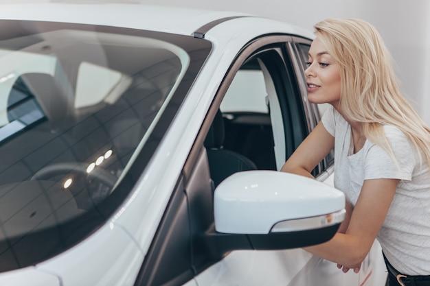 Mulher bonita, olhando para dentro de um carro novo no espaço da cópia do salão de concessionária Foto Premium