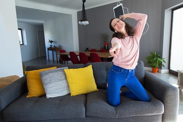 Mulher bonita, ouvir música e dançar no sofá Foto gratuita