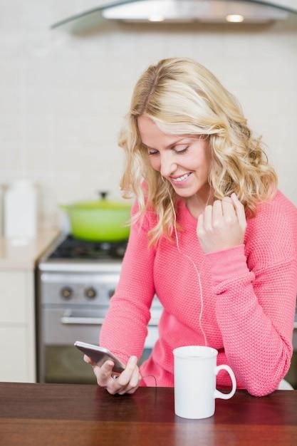 Mulher bonita ouvir música na cozinha Foto Premium