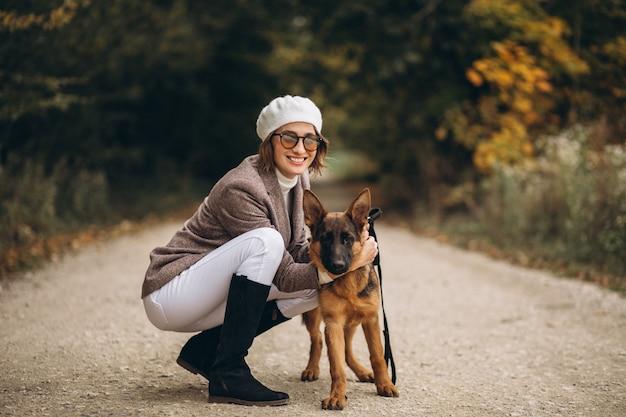 Mulher bonita, passeando com seu cachorro no parque outono Foto gratuita