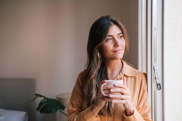Mulher bonita pela janela em casa bebendo chá Foto Premium