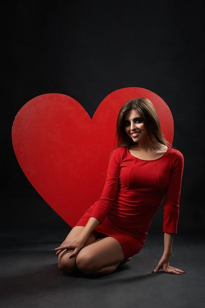 Mulher bonita posando com coração gigante no estúdio Foto gratuita