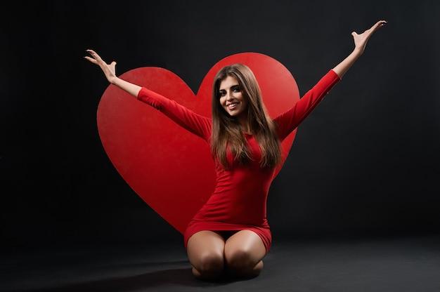 Mulher bonita posando com coração gigante Foto Premium
