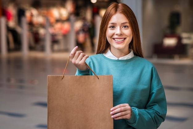 Mulher bonita posando com saco de papel Foto gratuita