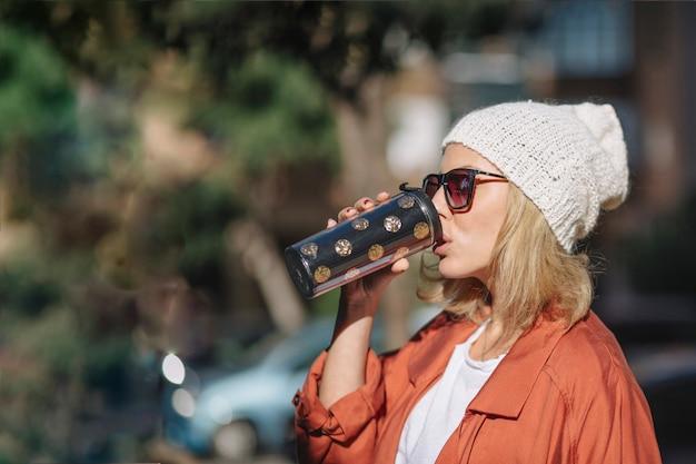 Mulher bonita que aprecia a bebida na rua Foto gratuita
