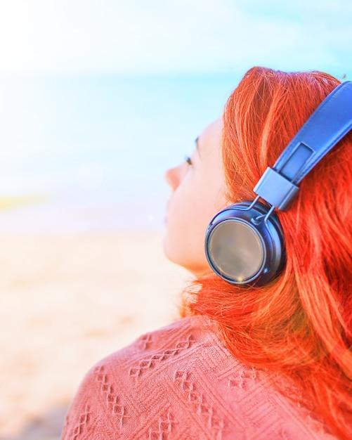 Mulher bonita que escuta a música na praia. jovem mulher ouvindo música com fones de ouvido. Foto Premium