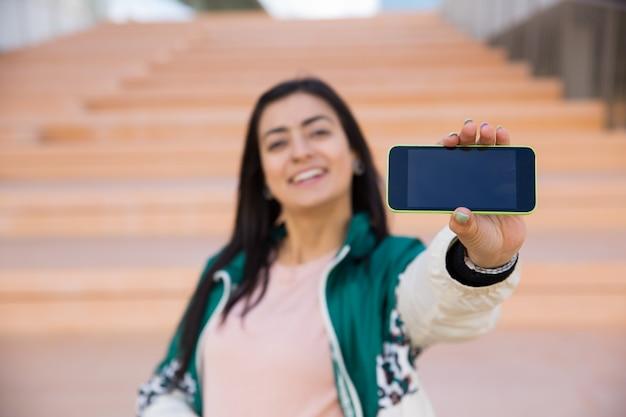 Mulher bonita que faz o selfie no telefone, sorrindo. gadget em foco Foto gratuita