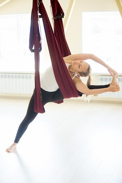 Mulher bonita que faz o yoga de visvamitrasana na hammock Foto gratuita