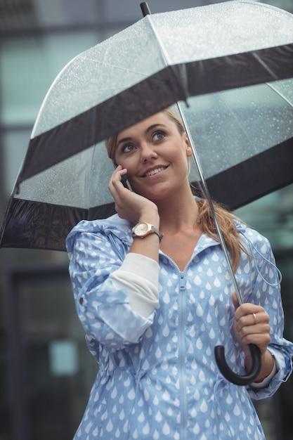 Mulher bonita que guarda o guarda-chuva ao falar no telefone móvel Foto gratuita